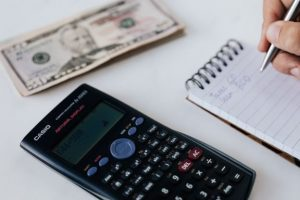 Closeup of a calculator, money and a notepad